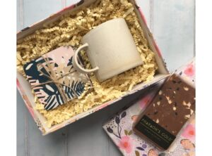 Floral gift box containing Rebecca Williams handmade ceramic mug, tropical pattern coasters and handmade fruit and nut chocolate.