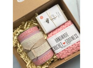 Kraft gift box containing Kica candles lavender rose and vanilla candle in up cycled tin, creature candy honey soap and handmade crocheted washcloth.